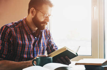 concentrated bearded man reading book