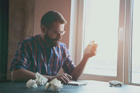 tearing: stressed bearded man writing with pen and tearing paper up