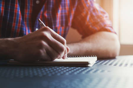 hand writing: male hand writing in notebook with pen