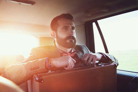 back seat: handsome bearded businessman sitting on back seat of car with  suitcase Stock Photo