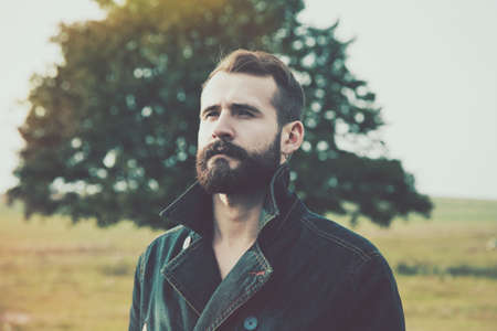 portrait of handsome bearded man with natural background