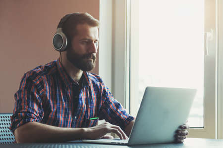 earphone: handsome bearded man  in headphones listening to music with laptop Stock Photo
