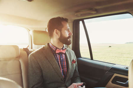 back seat: handsome bearded businessman sitting on back seat of car