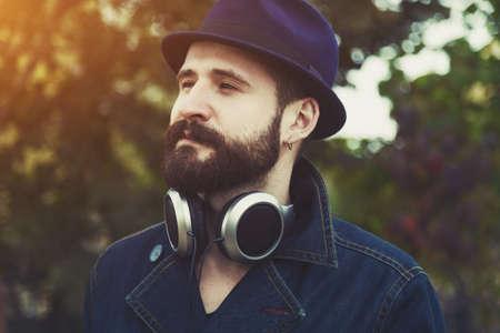 hombre con sombrero: hombre con barba y sombrero y los auriculares escuchando música Foto de archivo