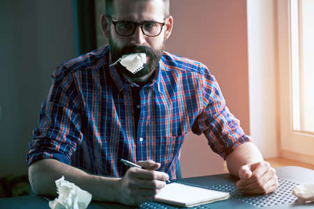 wrest: stressed bearded man writing with pen and making mistake or searching idea