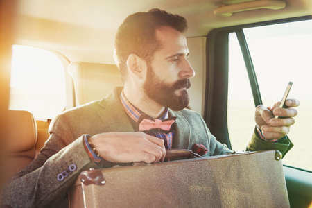 back seat: bearded businessman sitting on back seat of car with suitcase and touching phone with app Stock Photo