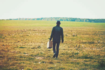 l'uomo va con la valigia in campo. Concetto di libertà, la solitudine o il concetto in viaggio