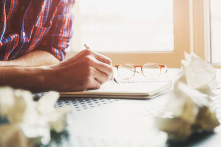 persona escribiendo: escritura de la mano en el cuaderno con las bolas de papel y lápiz Foto de archivo