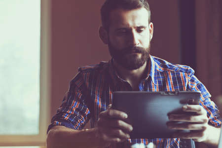 concentrated: concentrated bearded man sitting with digital tablet Stock Photo