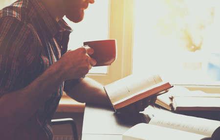 鬍子的男人閱讀書與咖啡或茶 版權商用圖片