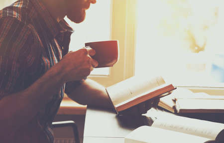 bearded man reading book with coffee or tea Stock Photo