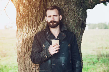 to go cup: Bearded man with paper cup of morning coffee in park