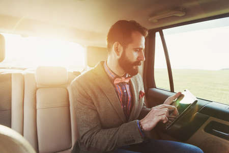 back seat: handsome bearded businessman sitting on back seat of car and touching digital tablet pc Stock Photo