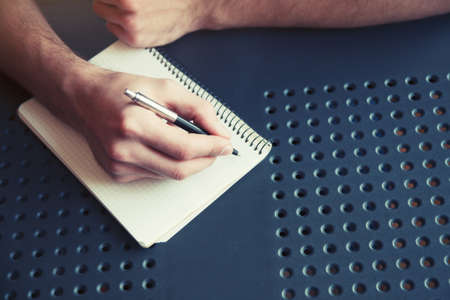 authors: male hand writing in notebook with pen