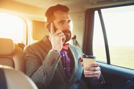 back seat: bearded businessman sitting on back seat of car with cup of coffee and talking on phone