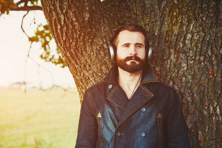 handsome bearded man  in headphones listening to music near natural tree