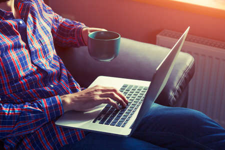 comfortable: man lying with laptop drinking coffee or tea