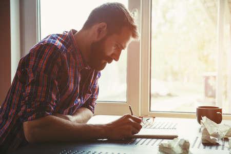 hombre escribiendo: Escritura del hombre de la barba en el cuaderno con las bolas de papel y lápiz