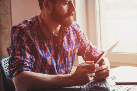 concentrated bearded man sitting with digital tablet 스톡 콘텐츠