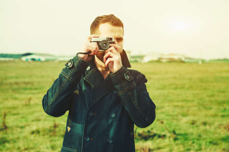 camera: Bearded man holding retro camera and taking photo