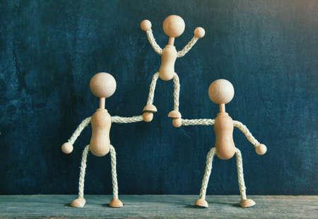 Twee houten weinig mannen het ondersteunen van de derde. Concept van teamwork, vriendschap, prestatie of familie Stockfoto