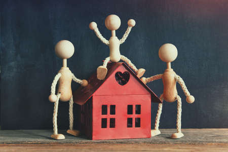 wooden little men with new house model Banco de Imagens