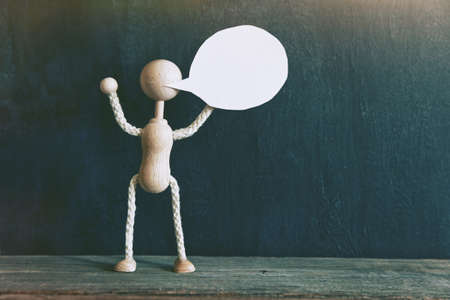 monologue: wooden little man holding an empty speech bubble on blackboard background