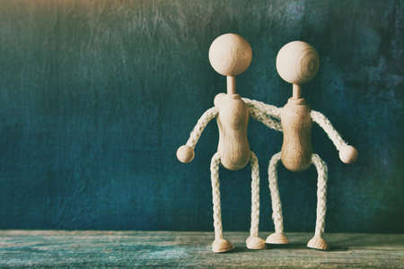 Two wooden little men hugging with copyspace. Love, friendship or teamwork concept