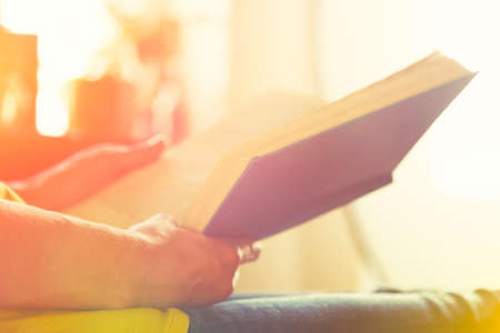 hands holding book and reading in sunlight