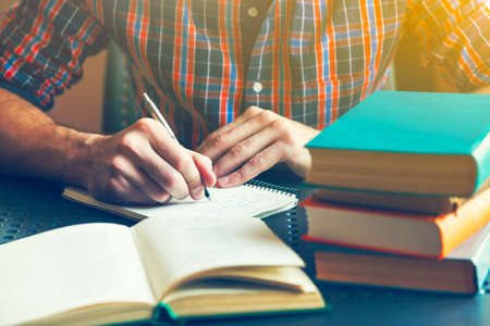 hand writing: male hand writing with pen near books Stock Photo