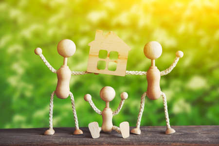 wooden little men with new house model Stock Photo
