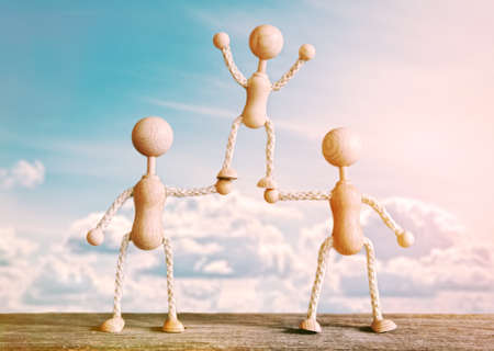 teamwork concept: Two wooden little men supporting the third. Concept of teamwork, friendship, achievement or family