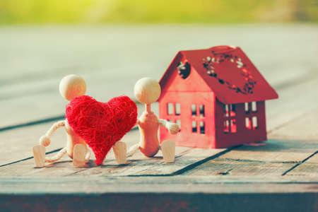 convivencia familiar: Dos pequeños hombres de madera con el corazón casa cerca