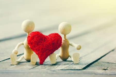 Dos pequeños hombres de madera con corazón. Concepto de amor o tarjeta de San Valentín Foto de archivo - 61534193