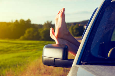 descansando: Woman legs out car window. Freedom or travelling concept