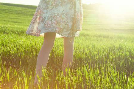 girls legs walking in field in morning sun light Banque d'images