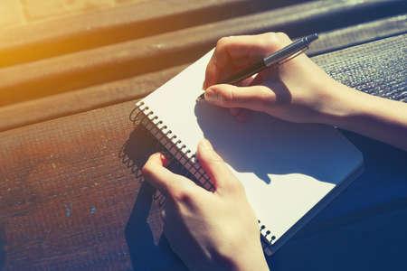 소녀는 나무 책상에 펜으로 작성으로 손 스톡 콘텐츠