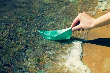 boats: hand with paper boat near water