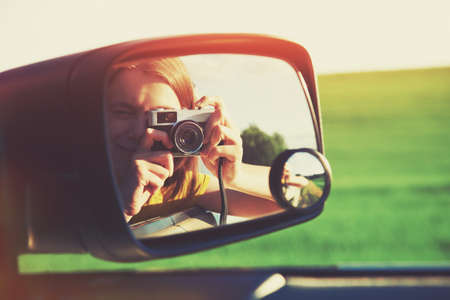 smiling girl taking photo with camera moving in car