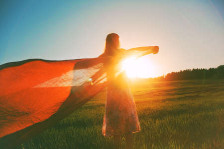 woman in field: girl looking at magical sunrise with tissue as inspiration for new day