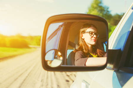 smiling girl with glasses driving car in mirror reflection Stok Fotoğraf