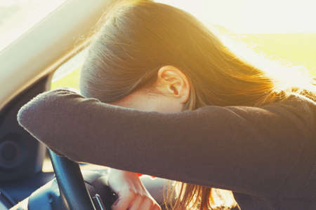 sad lady: stressed or tired girl in car lying on steering wheel