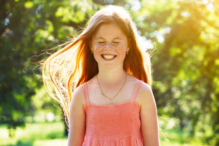 Portrait of smiling redhead girl with freckles in summer sun Фото со стока