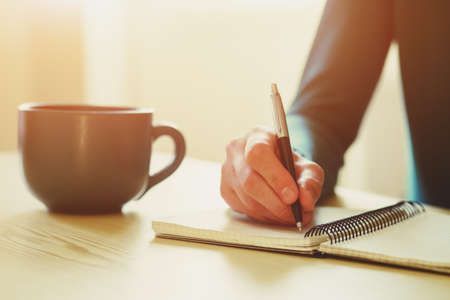 copybook: hands with pen writing on notebook with morning coffee or tea