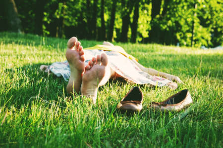 girl lying in grass barefoot without shoes in summer sun