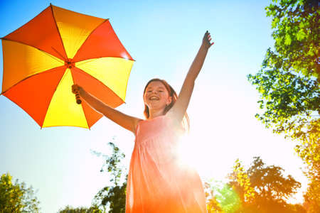 Happy redhead girl with umbrella in summer sun. Freedom, summer, childhood concept