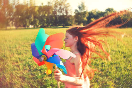 Happy redhead girl with pinwheel toy in motion blur. Freedom, summer, childhood concept