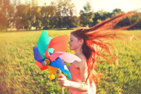 Gelukkig roodharige meisje met pinwheel speelgoed in beweging vervagen. Vrijheid, zomer, jeugdconcept