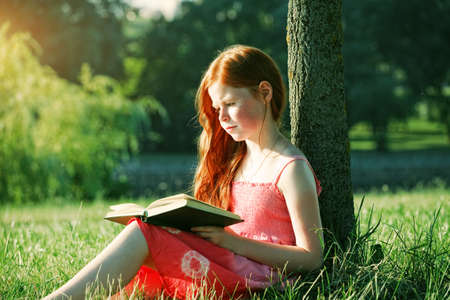 little redhead girl reading book at nature