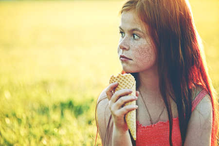 redhaired: pretty redhead girl with freckles eating ice cream. space for text